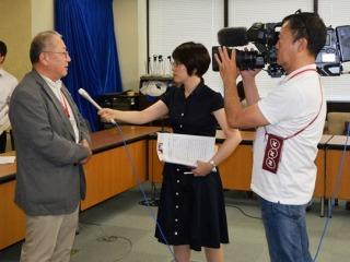 NHKからの取材を受ける、鈴木常任理事。